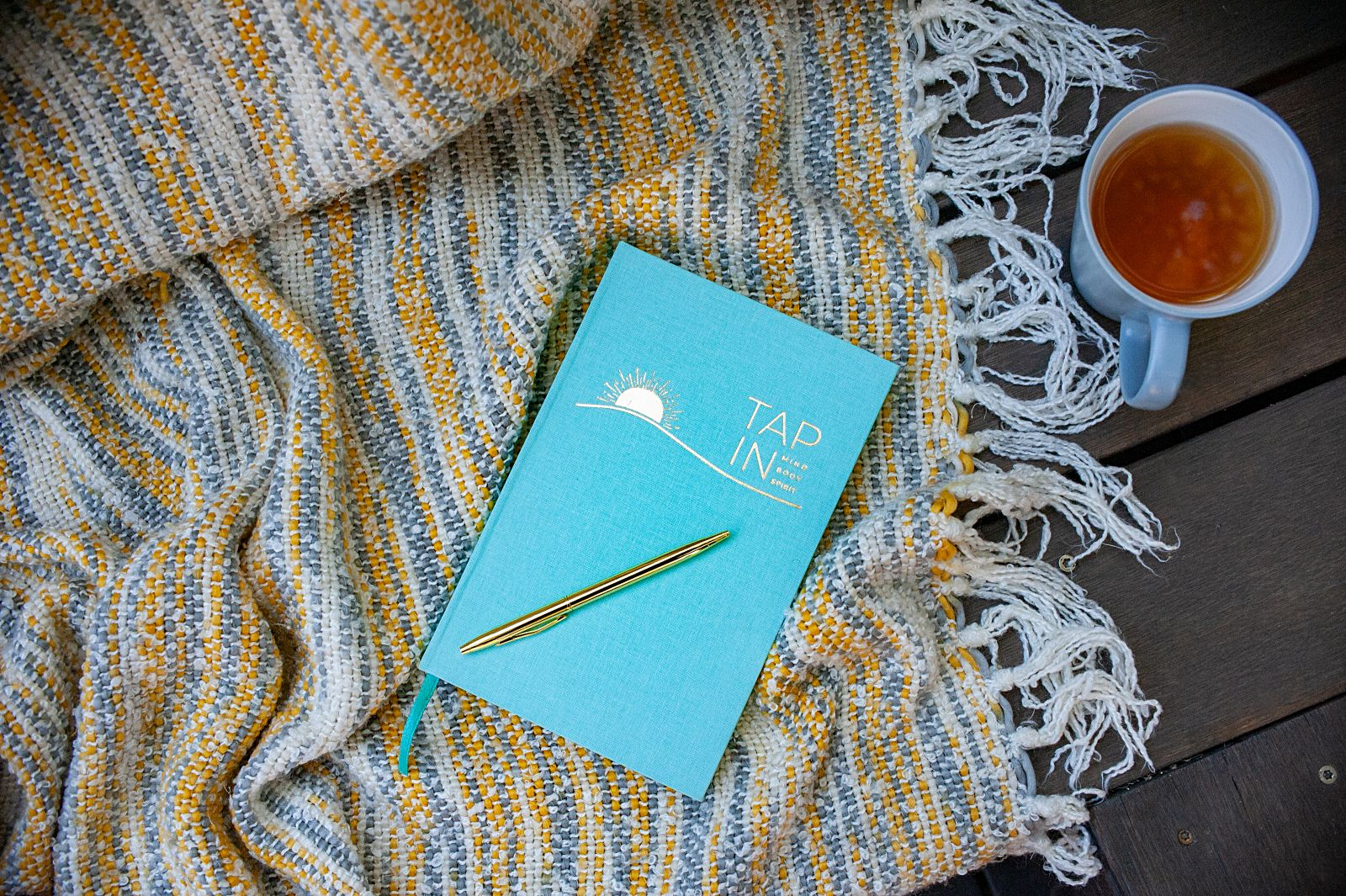 TAP IN wellness journal on a yellow blanket for a wellness retreat